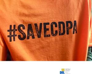 Image description: #SAVECDPA printed on an orange t-shirt]